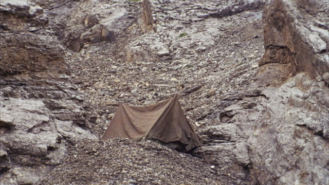 MEDIUM ANGLE OF BROWN TENT PERCHED ON LEDGE OF GREY AND RUST COLORED ROCKY SLOPE. SEE VARIOUS DIRT AND ROCKS ALONG SLOPE. PULL BACK TO SEE FULL EXTENT OF ROCKY SLOPE.