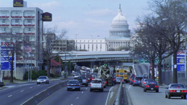 wide angle of cars driving on freeway or expressway and capitol building in bg. ford sedan driving on left side of freeway. - exxon stock videos & royalty-free footage