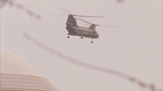 wide angle of chinook military helicopter flying over domed roof of the thomas jefferson memorial. tree branches in fg, could be cherry trees. - military helicopter stock videos and b-roll footage