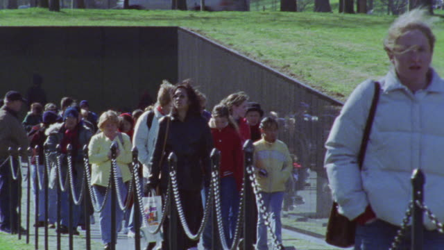 hand held of people walking past vietnam veterans memorial on walk way. tourists. landmarks. camera moves around erratically. - vietnam veterans memorial video stock e b–roll