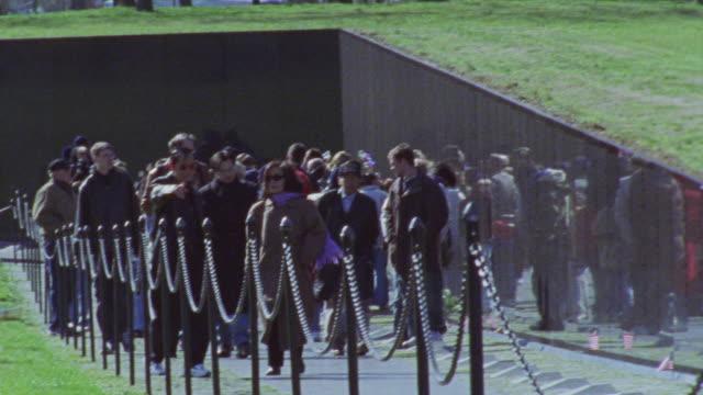 wide angle of people walking past vietnam veterans memorial on walk way. tourists. landmarks. - vietnam veterans memorial video stock e b–roll