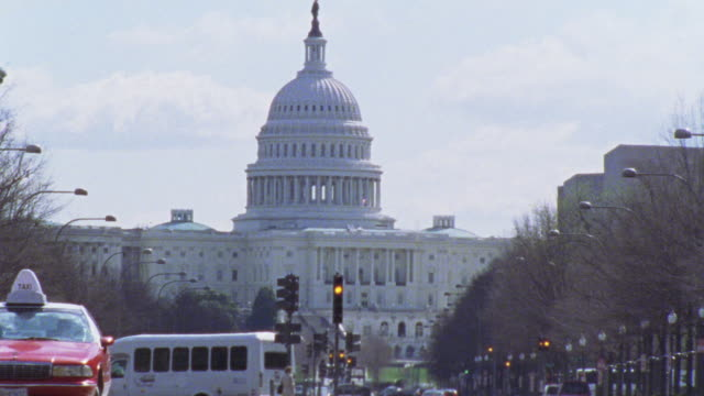vídeos de stock, filmes e b-roll de est ms capitol hill. see ongoing traffic in fg. cars. capitol building. domed government office building. - capitol hill