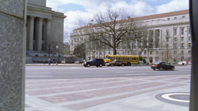 stockvideo's en b-roll-footage met wide angle of cars driving on city street, pennsylvania avenue past national archive building. brick courtyard in fg. people walking on sidewalk. government building. - national archives washington dc