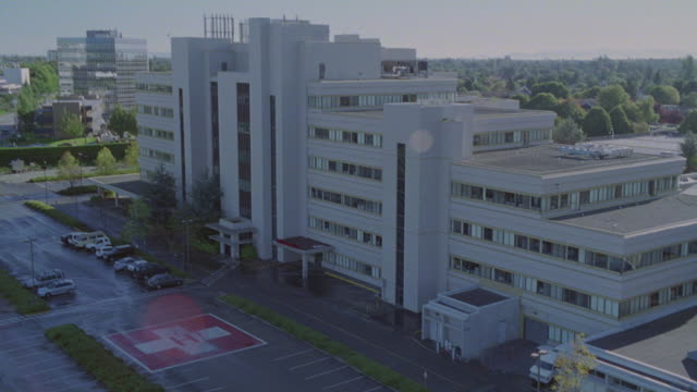 AERIAL SHOT OF LARGE HOSPITAL WITH PARKING LOT IN FRONT. PANS AND ZOOMS IN AND OUT ON BUILDING.<P><A HREF='HTTPS://WWW.SONYPICTURESSTOCKFOOTAGE.COM/FOOTAGE?KID=4303'>FOR DAY-NIGHT MATCHING SHOTS, CLICK HERE.</A><P>