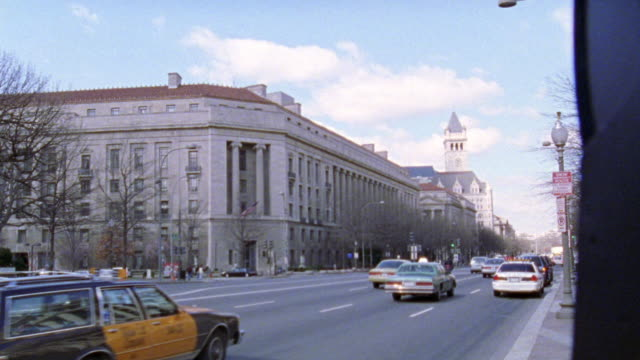 WIDE ANGLE OF CARS DRIVING ON CITY STREET, PENNSYLVANIA AVENUE, PAST US DEPARTMENT OF JUSTICE BUILDING. GOVERNMENT BUILDINGS. MULTI-STORY BUILDINGS. ROBERT F. KENNEDY DEPARTMENT OF JUSTICE BUILDING.
