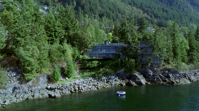 aerial of modern two-story upper class house in mountains. see large inner tube floating in lake in front of house. much vegetation around house in mountains. - zweistöckiges bauwerk stock-videos und b-roll-filmmaterial
