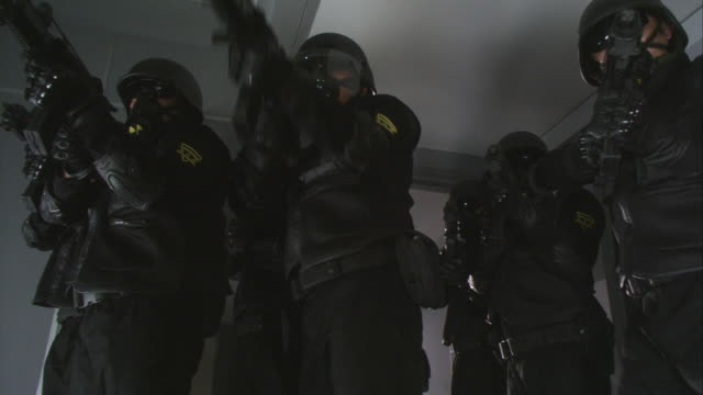 up angle of gray double doors. see swat team members open doors and position for attack. see swat team with machine guns and gas masks. futuristic. - weaponry stock videos & royalty-free footage
