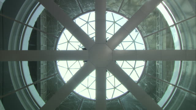 vídeos de stock e filmes b-roll de up angle of skylight window. see intricate patterns on windows. see people or men walking out of center of window. see people dressed in black. camera pans down. futuristic. - claraboia