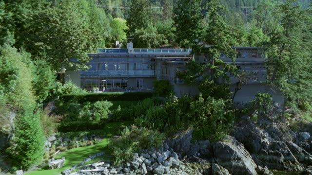 aerial of modern two-story upper class house in mountains. see lake in front of house. much vegetation around house in mountains. - zweistöckiges bauwerk stock-videos und b-roll-filmmaterial