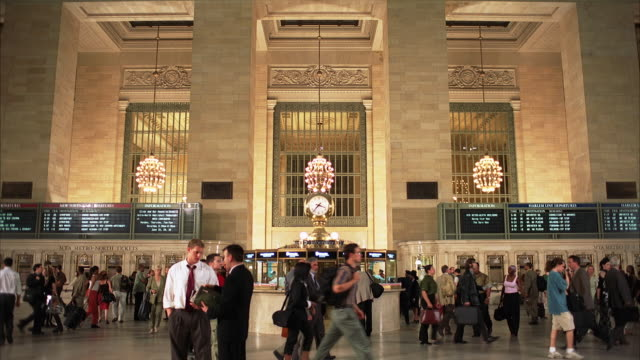 PAN DOWN OF GRAND CENTRAL STATION. LARGE CROWDS OF PEOPLE, MEN, WOMEN WALKING AROUND.  TRAIN STATIONS, SUBWAY STATIONS.