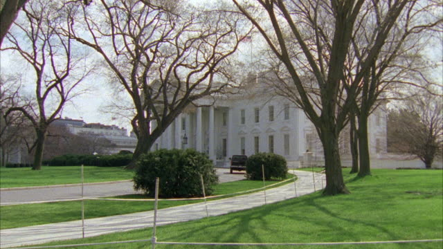 wide angle on the white house. white house viewed from lawn. barren trees suggest winter season. government building. - weißes haus stock-videos und b-roll-filmmaterial