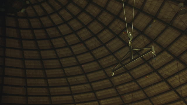 up angle of male acrobat spinning and somersaulting suspended from wires in circus dome. acrobat is wearing purple and green spandex suit. - spandex stock videos & royalty-free footage