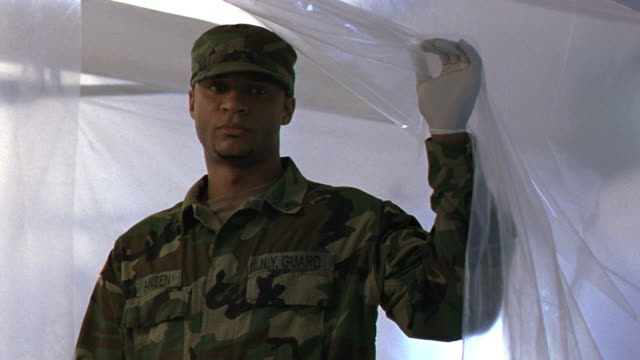 medium angle of plastic sheet. army soldier with latex gloves on lifts sheet, stares sadly at what he sees. medical centers. - ラテックス点の映像素材/bロール