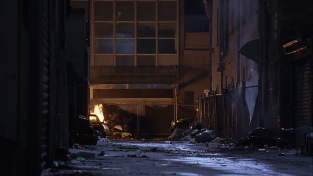 wide angle of urban area alley with trash fire. hummer and military vehicle driving, turn down alley. flames. - hummer stock videos and b-roll footage