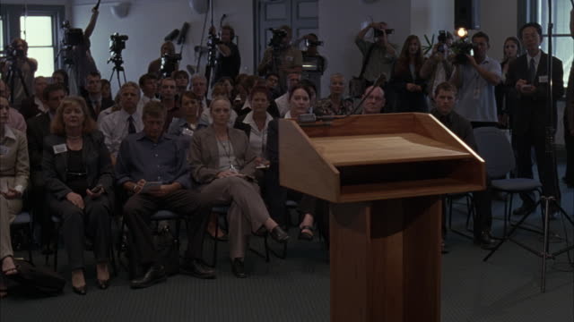 wide angle of conference room or press room filled with men and women reporters sitting in chairs. people wear badges. - press conference stock videos and b-roll footage