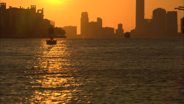 pan up of miami harbor at sunset.  see buoys, construction cranes in harbor, city skyline, setting sun. pan down, end on water. - buoy stock videos & royalty-free footage