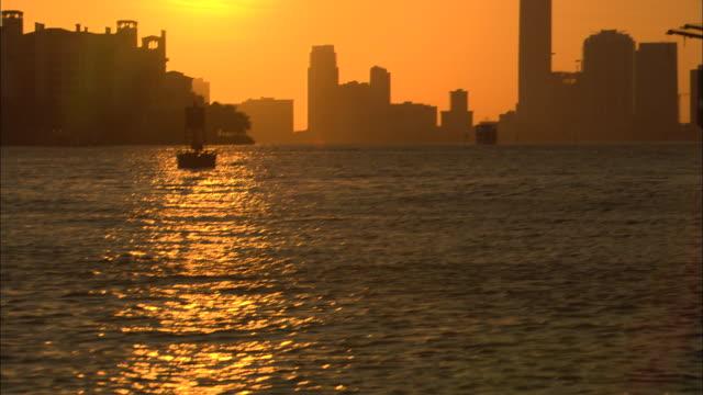 vídeos de stock, filmes e b-roll de pan up of miami harbor at sunset.  see buoys, construction cranes in harbor, city skyline, setting sun. pan down, end on water. - boia equipamento marítimo de segurança