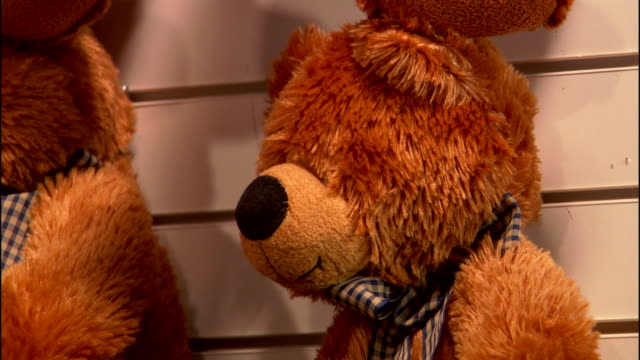 CLOSE ANGLE OF BROWN PLUSH STUFFED BEARS  OR TOYS ON DISPLAY AT CARNIVAL OR FAIR BOOTH.