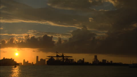 wide angle of miami harbor at sunset.  see ships, construction cranes in harbor, city skyline, setting sun and clouds. - miami stock videos & royalty-free footage