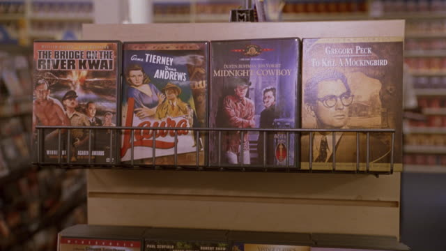 medium angle of shelves in video store, vhs cassette tape copies of to kill a mockingbird, bridge on the river kwai, midnight cowboy. - cassette tape stock videos & royalty-free footage