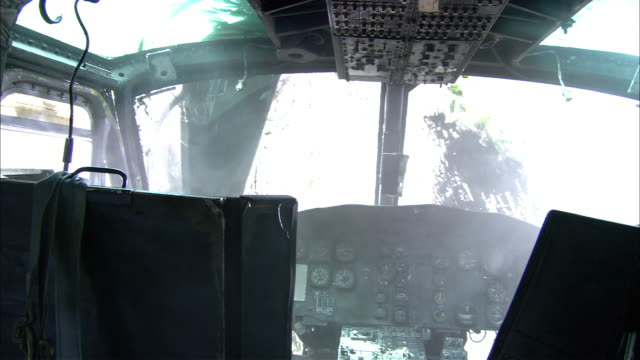 medium angle of cockpit of crashed military helicopter on ground. trees faintly visible in sunlight outside. - military helicopter stock videos and b-roll footage