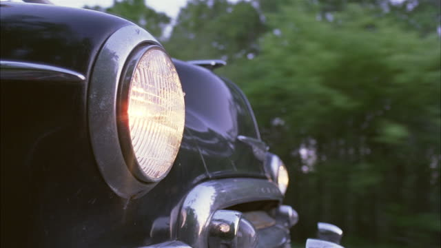 medium angle, driving pov bumper cam straight left of the front of a classic car driving highway lined with trees.  chrome-rimmed headlights seen turning on and off. - collector's car stock videos and b-roll footage