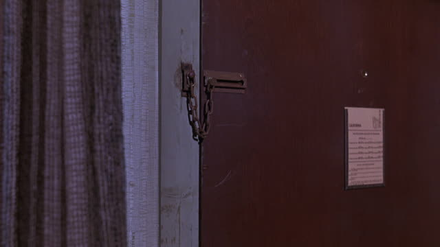close angle of lower class motel room door with security door chain. door shakes as if person is trying to break in. locks. - door chain stock videos & royalty-free footage