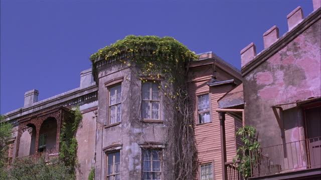 zoom in of three story house or apartment building with brick walls, octagonal bay window rooms, ivy on side.  a bit rundown.  could be lower class. shot tilts up as it dollies in. - erkerfenster stock-videos und b-roll-filmmaterial