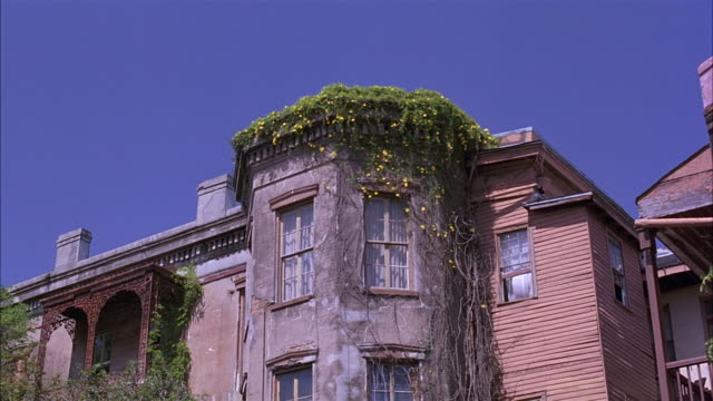 pull back of three story house or apartment building with brick walls, octagonal bay window rooms, ivy on side.  a bit rundown.  could be lower class. shot tilts up as it dollies in. - erkerfenster stock-videos und b-roll-filmmaterial