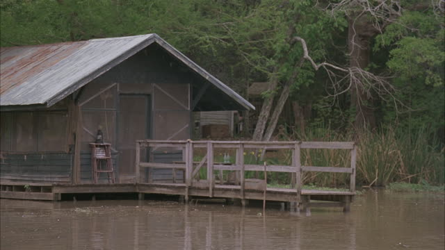 vidéos et rushes de wide angle of dock, shack on muddy river.  zoom out and pan down to muddy, rippled water.  trees. - cahute