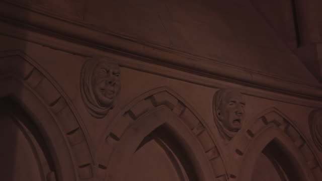 close angle of marble heads of catholic priests or other religious figures on church wall. camera pans left to right along wall. heads are placed along church arches. - marble wall stock videos and b-roll footage