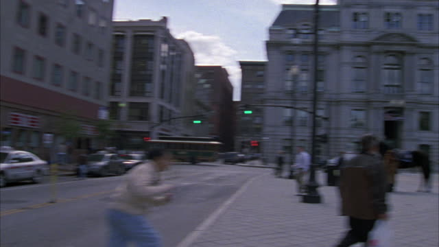 HAND HELD ANGLE OF A POLICE OFFICER WITH A HORSE TALKING TO SEVERAL PEDESTRIANS ON A CITY STREET. THE CAMERA PANS DOWN A LARGE STONE BUILDING TO THE PEDESTRIANS IN THE STREET.