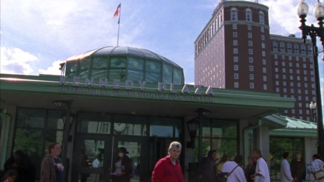"""HAND HELD ANGLE OF TUE KENNEDY PLAZA INTERMODAL TRANSPORTATION CENTER.  PEOPLE AND PEDESTRIANS WALK OUT OF THE TRAIN STATION OR BUS STATION. """"FINANCIAL DISTRICT EAST APPROACH STREET"""" ON A STREET SIGN."""