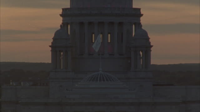 HAND HELD ANGLE MOVING BACK AND FORTH FROM A DOWNTOWN CITY STREET TO THE RHODE ISLAND STATE HOUSE CAPITOL BUILDING TO A SUNSET.