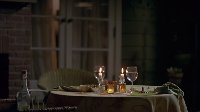 medium angle of small circular table set for two people. food on plates, wine glasses are filled. lit candles in candle sticks holders and votive candle holders on table. - votive candle stock videos and b-roll footage