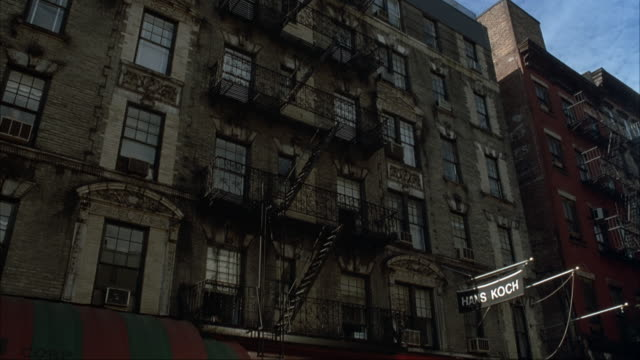 """up angle of five story apartment building above """"hans koch"""" store. building is made of gray bricks. see fire escape down front of building. - fire escape stock videos and b-roll footage"""