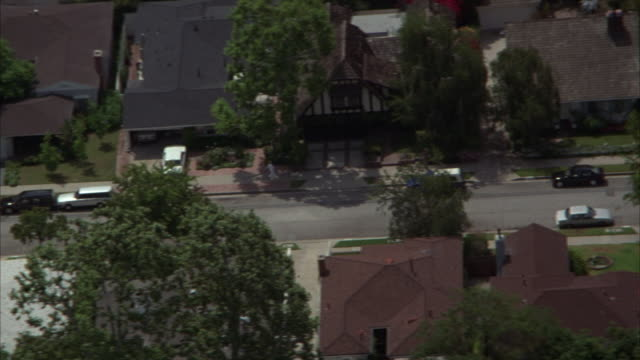 high angle down tracking shot of off-white pickup truck driving through middle class residential area. - middle class stock videos and b-roll footage