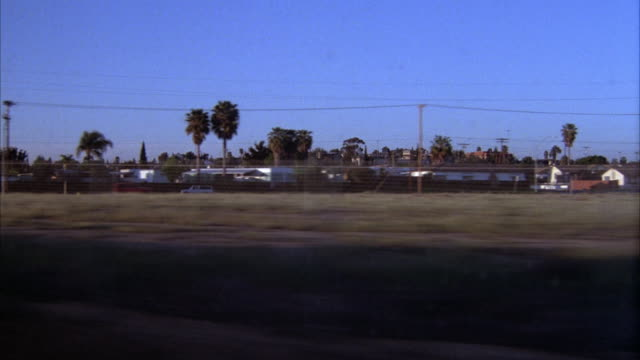 vidéos et rushes de medium angle moving pov from passenger side of train car or trolley. see empty grass lot in foreground and trailer park in background. - san diego