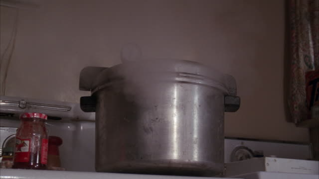 vidéos et rushes de close angle of metal cooking pot or pressure cooker on stove. see gauge on top of pot either measuring temperature or pressure. - cuisinière