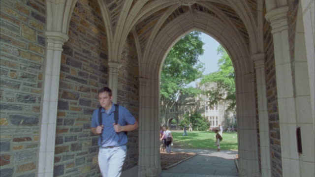 wide angle of people, could be college students, walking through courtyard visible through brick and stone archway. - ivy league university stock videos and b-roll footage