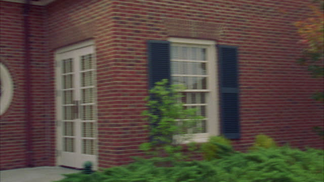 pan right to left of two story colonial style brick building with white french doors. dormer windows.  hunter green shutters. - shutter stock videos & royalty-free footage