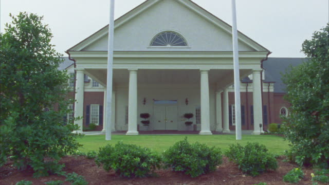 PAN DOWN FROM AMERICAN FLAG AND NORTH CAROLINA FLAG FLYING IN FRONT OF COLONIAL STYLE BRICK BUILDING WITH COLUMNS AND COVERED DRIVEWAY.
