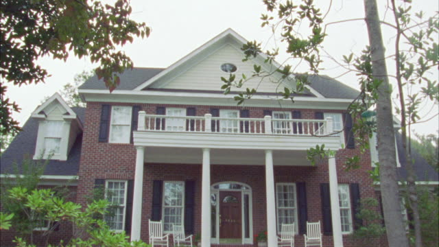 pan down from tree branches to front of two story upper class brick house with white columns, balcony, and rocking chairs on front porch. - brick house stock videos & royalty-free footage
