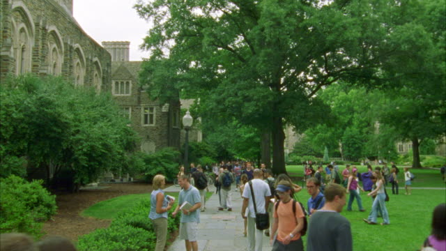 wide angle of college students walking on sidewalks in courtyard or quad with grass and trees. two story stone building on left side of screen. could be college, university or ivy league campus. - ivy league university stock videos and b-roll footage