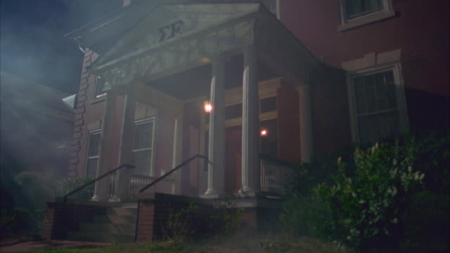 stockvideo's en b-roll-footage met pull back of two story brick sigma epsilon fraternity house with white columns and porch. hanging light above entrance is on, swings gently. - bare tree