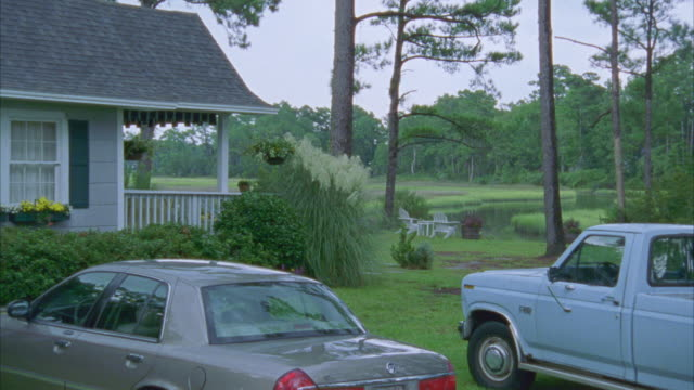 medium angle of blue pickup truck and grey lincoln town car parked in front of one story, middle class house in countryside or rural area. - lincoln town car stock videos and b-roll footage