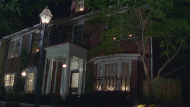 "pan down from tree branches in fg to two story middle or upper class brick row house with lights on. lamp post in fg. matching day ""2029-011 two story"" - brick house stock videos and b-roll footage"