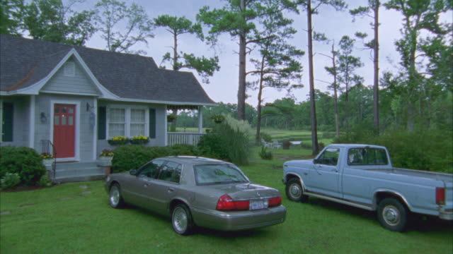 medium angle of middle class, one story house with blue pick up truck ford f150 and grey lincoln town car parked in front on the grass. trees, woods and creek or stream in bg. could be in countryside or rural area. - lincoln town car stock videos and b-roll footage