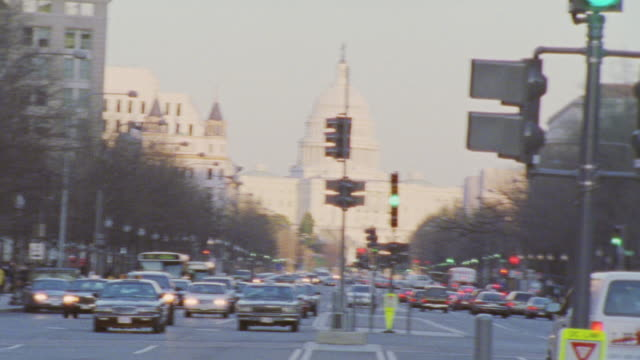 HAND HELD OF CARS DRIVING ON CITY STREET. CAPITOL BUILDING IN BG. CAMERA TRACKS A JEEP GRAND CHEROKEE AS IT DRIVES BY.