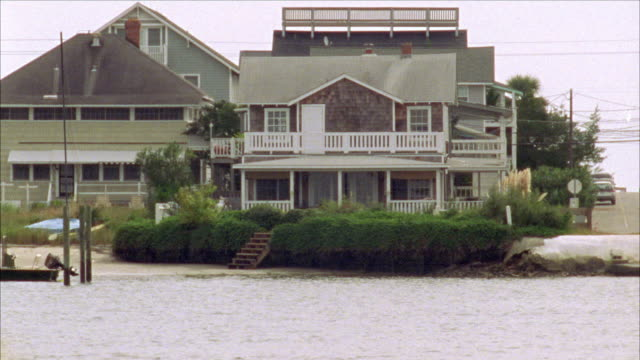 pan up from water to upper class, two story, shingle style beach house. wooden steps lead down to small sandy beach and calm water. could be in bay or cove. small motorboat tied to wooden pillar in water. - zweistöckiges bauwerk stock-videos und b-roll-filmmaterial